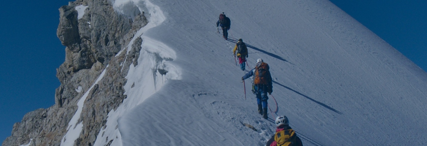 Mountain climbers scaling a snowy peak