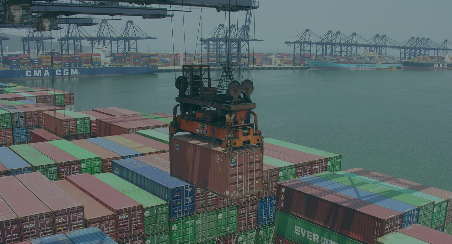 Image of a container port with ships in the background.